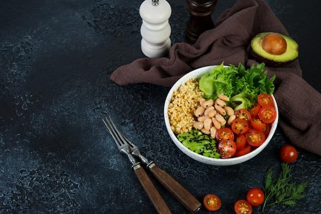 Вегетарианская салатница на черном фоне бетона в тарелку. салат из булгура и свежих овощей. концепция чистого и здорового питания. горизонтальное фото с копией пространства