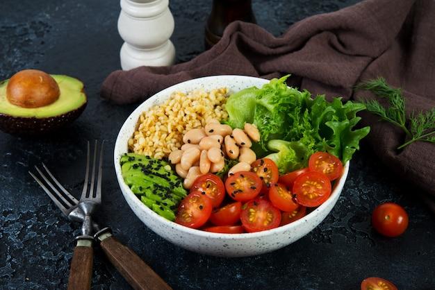 Вегетарианская салатница на черном фоне бетона в тарелку. салат из булгура и свежих овощей. концепция чистого и здорового питания. горизонтальное фото.