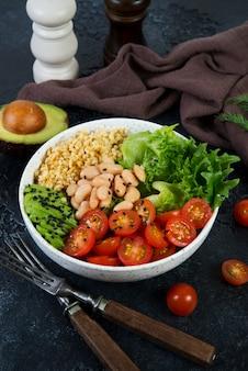 Вегетарианская салатница на черном фоне бетона в тарелку. салат из булгура и свежих овощей. концепция чистого и здорового питания. вертикальное фото
