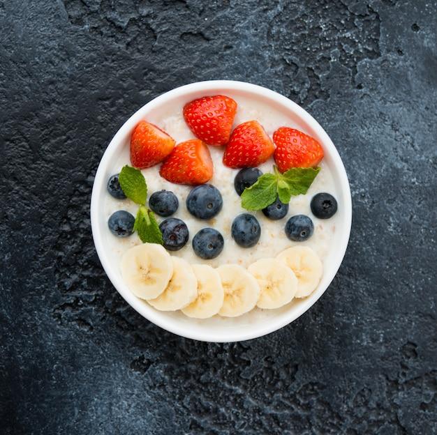 コンクリートの壁の左側の皿にベリーとフルーツが入ったオートミールの美味しくて健康的でバランスのとれた朝食。水平方向。上面図