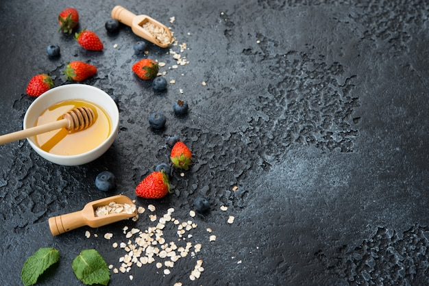 健康的でバランスのとれた朝食の材料は、スペースを利用してコンクリートの壁に配置されています。オートミール、ベリー、蜂蜜。