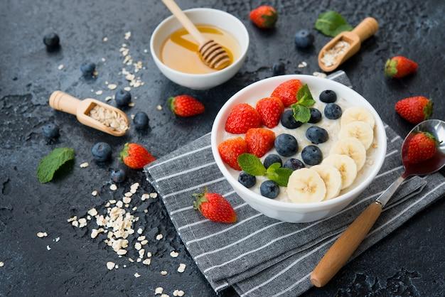 コンクリートの壁の左側の皿にベリーとフルーツが入ったオートミールの美味しくて健康的でバランスのとれた朝食。コピースペース付きの水平方向。