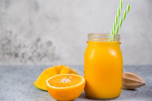 オレンジ色の瓶とマンゴーのスムージーが灰色のコンクリートの壁に立っています。菜食主義者のための清潔で健康的な食品。健康的なダイエット。水平方向。