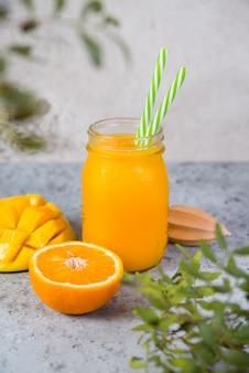 瓶にオレンジとチューブを入れたマンゴースムージーは、灰色のコンクリートの壁の上に立って、周りは緑の葉です。菜食主義者のための清潔で健康的な食品。健康的なダイエット。