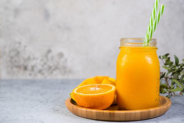 オレンジ色の瓶入りとチューブ入りのマンゴースムージーが、右側の灰色のコンクリートの壁に立っています。菜食主義者のための清潔で健康的な食品。健康的なダイエット。コピースペース。