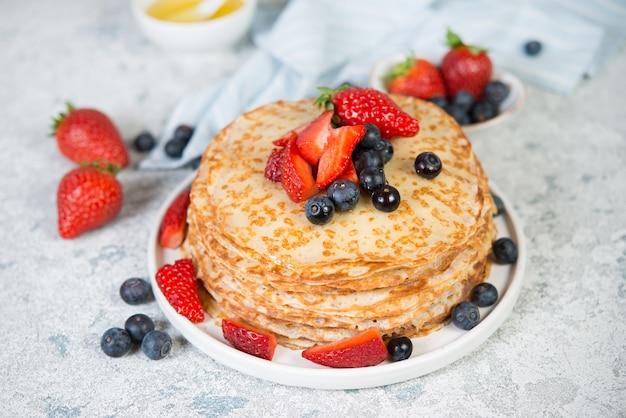 Тонкие домашние блины в тарелку со свежими ягодами и медом.