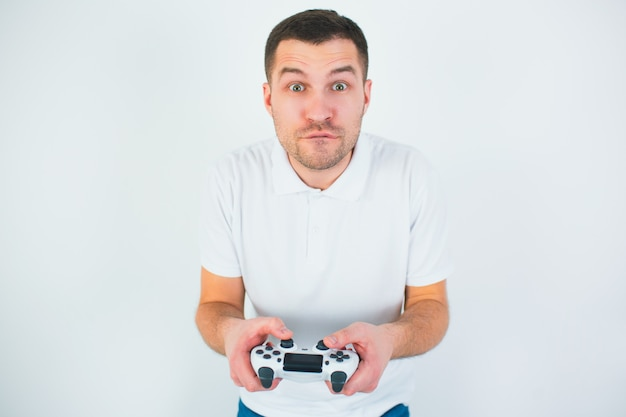 Молодой человек изолированный над белой стеной. парень держит джойстик в руках и играет в компьютерную игру. сосредоточены на игре.