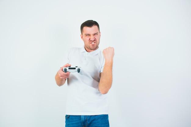 Молодой человек изолированный над белой стеной. парень подбадривает довольным криком из-за победы в компьютерной игре. держа в руке джойстик. игра в игры во время карантина.