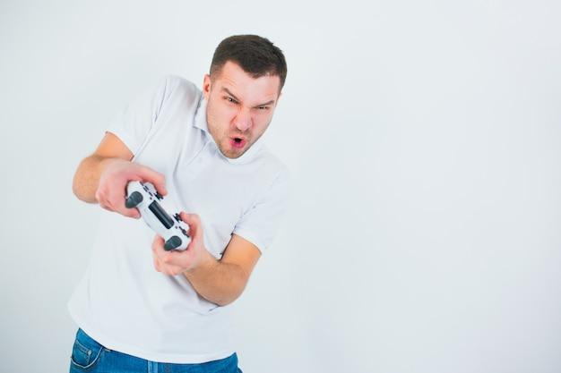 Молодой человек изолированный над белой стеной. активный парень играет в игры во время карантина. держите джойстик обеими руками во время интенсивного матча.