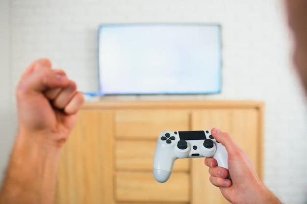 Молодой человек сидеть в комнате, держа джойстик в одной руке и кулак с другой. играя в компьютерные игры по телевизору. игровой досуг.