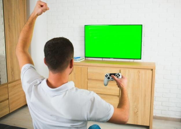 Молодой человек сидеть в комнате, играя в компьютерные игры, используя джойстик и телевизор.