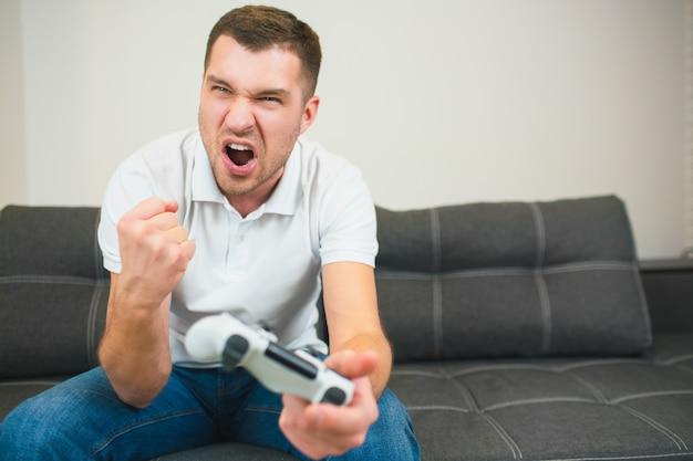 Молодой человек сидеть в комнате, играя в компьютерные игры. самец держит в руке джойстик и развеселит с удовольствием. кричать и кричать во время игры.