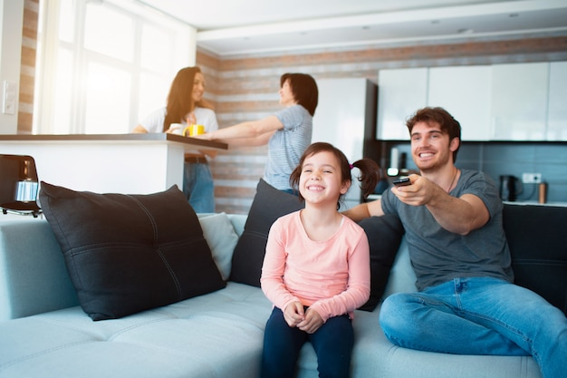 Большая семья дома. мама и дочка общаются друг с другом. отец или брат смотрят телевизор.