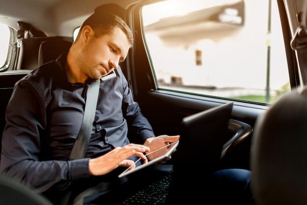 タクシーで忙しいビジネスマン。マルチタスクの概念。乗客は後部座席に乗り、同時に作業します。スマートフォンで話し、ラップトップとタブレットを使用します。