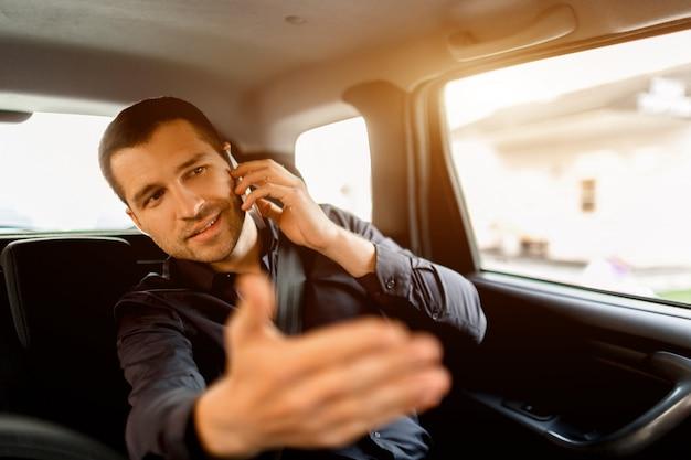 タクシーで忙しいビジネスマン。マルチタスクの概念。乗客は後部座席に乗り、同時に作業します。スマートフォンで話し、ドライバーと通信する