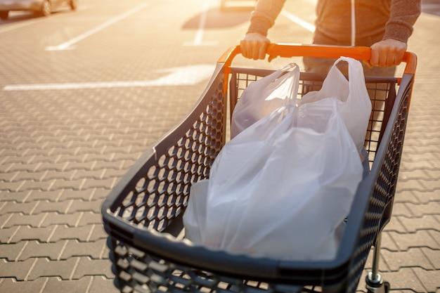 郊外のショッピングセンターにある大きなスーパーマーケットの近くに食べ物が入ったベビーカーのクローズアップ。ショッピングに成功した後、駐車場で車の近くに立っている男性