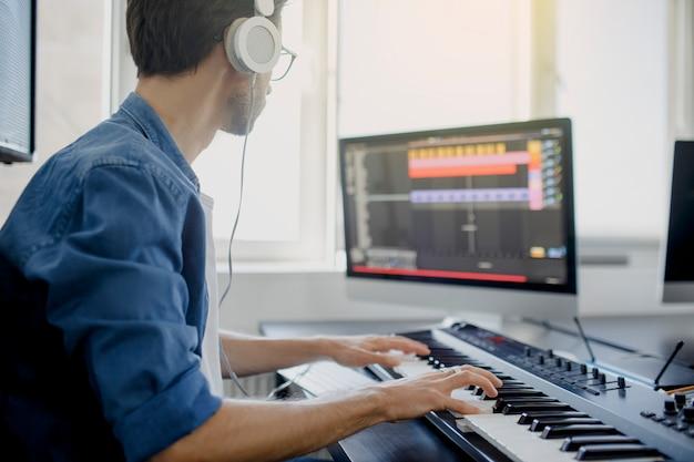 作曲家は、レコーディングスタジオでピアノの鍵盤を手にします。音楽制作技術、ピアニオと机の上のコンピューターのキーボードに取り組んでいる男。