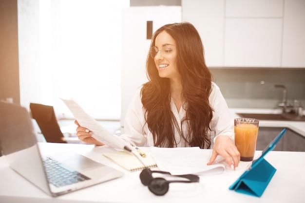 Красивая черноволосая женщина работает из дома. сотрудник сидит на кухне, много работает над ноутбуком и планшетом, проводит видеоконференции и встречи.