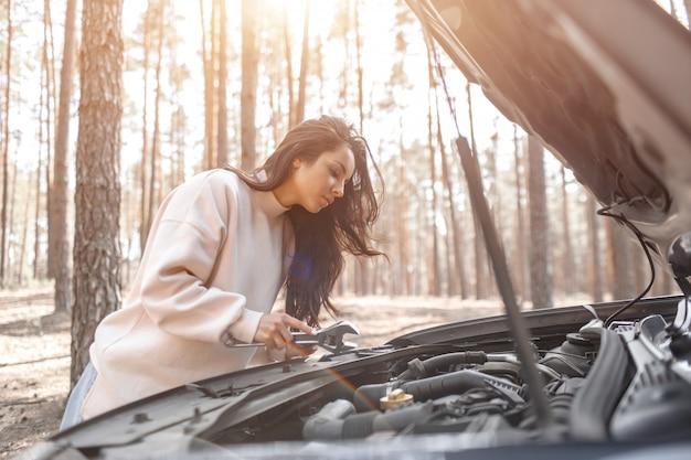 車が故障した。道路での事故。女性がボンネットを開けて、エンジンと車のその他の詳細をチェックしています