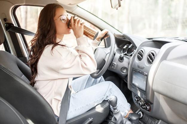 お車でお越しのカントリートリップ。女性モデルは、魔法瓶からコーヒーやお茶を飲みます。