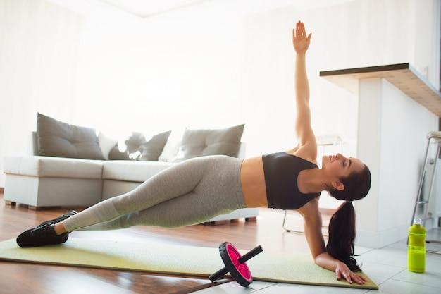 Молодая женщина делает спортивные тренировки в комнате во время карантина. встаньте на одну сторону доски и держите одну руку вверх. посмотри на потолок. гимнастика дома.