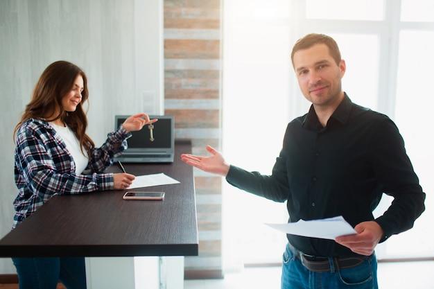 Риэлтор, брокер или арендодатель показывает квартиру молодой женщине. она собирается подписать договор аренды с ним.