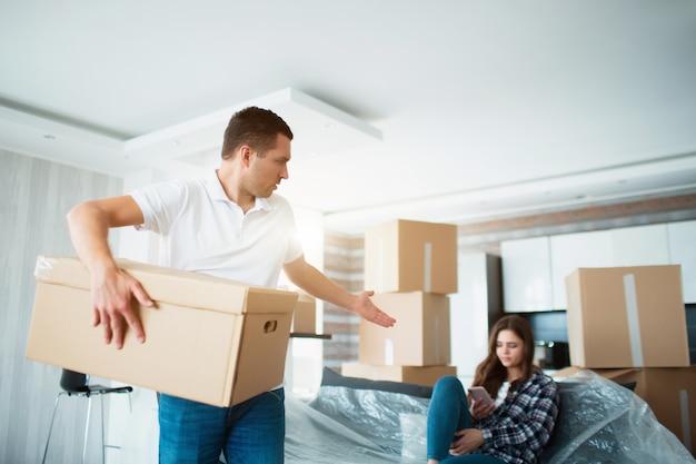 移動との関係の概念。彼は満足していません。夫は箱を開梱します。その間、妻は何もしません。彼女は友達と話すことを好みます。夫は満足していません。