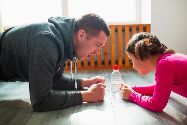 若い父親と彼のかわいい小さな娘は、家の床で板をやっています。家族のフィットネストレーニング。かわいい子供とパパは室内のマットでトレーニングをしていて、部屋の窓の近くでエクササイズをしています。