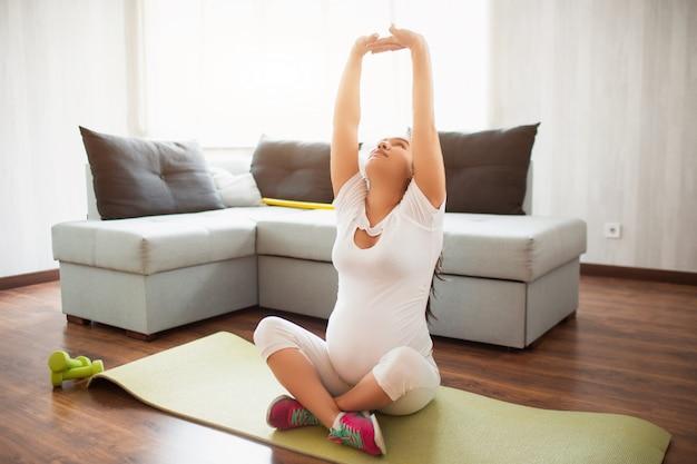 Беременная женщина работает на коврик для йоги в домашних условиях. беременность и спорт. йога и пилатес для беременных. третий триместр беременности