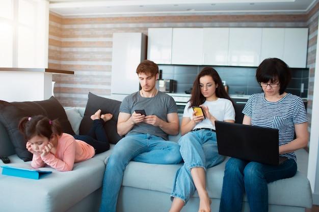 Большая семья дома. каждый использует свой гаджет. зависимость от социальных сетей и мобильных игр. планшет, смартфон и ноутбук вместо веселья разговаривают вечером