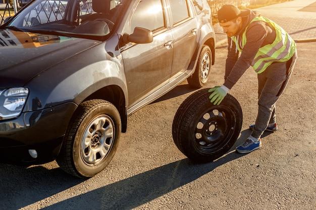 ドライバーは古いホイールをスペアと交換する必要があります。車の故障後にホイールを変更する男。交通、旅行のコンセプト