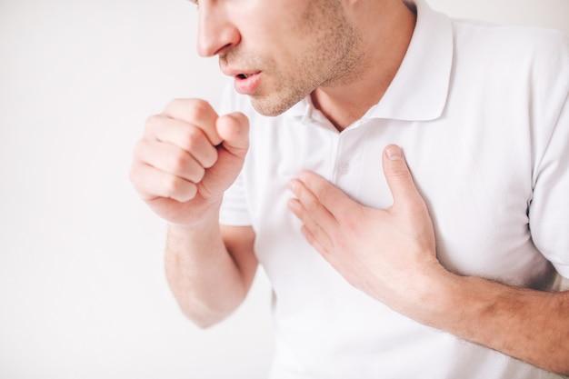 若い病気の男は白い背景で隔離されました。ビューをカットし、口と咳の近くに拳を握っている男のクローズアップ