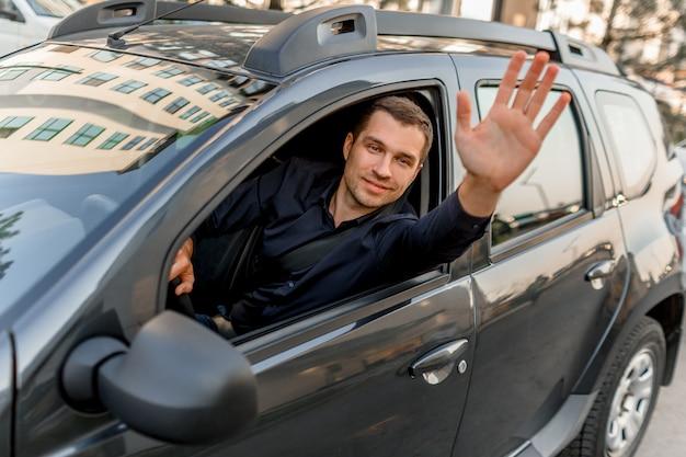シャツを着た若い男性が車に座って、誰かに手を振っています。タクシーの運転手は外を見て微笑みます。都市環境と交通
