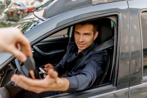シャツを着た若い男が車に座っています。ディラーは彼に新しい車の鍵を与える。自動車販売、都市環境、交通コンセプト