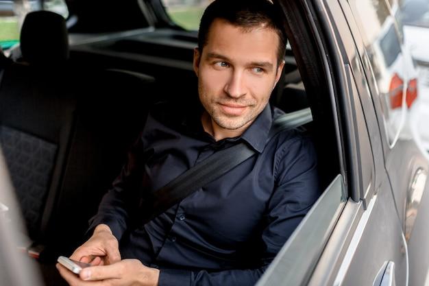 タクシーのビジネスマンがスマートフォンを持っていると、窓の外を見ています。後部座席のポートレートで乗客