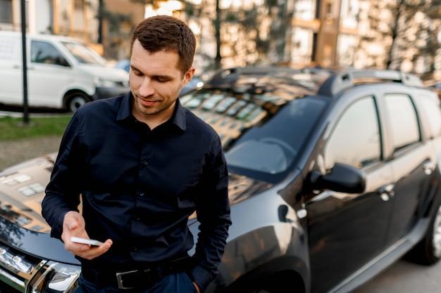 車の近くの通りに立っている若い男や暗いシャツを着たビジネスマンがスマートフォンを見ます。運転手は乗客またはクライアントを待っています。都市交通のコンセプト