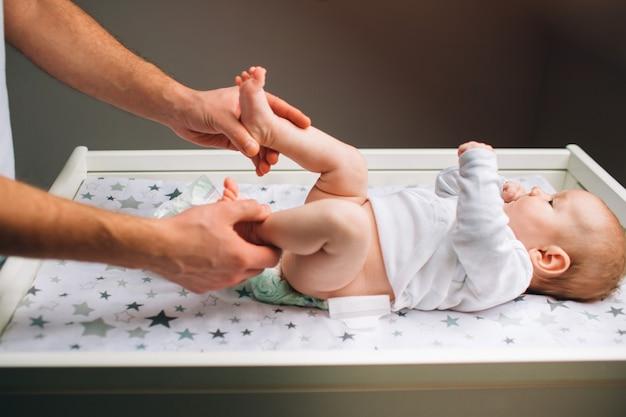 Отец и новорожденный ребенок в детской. мама делает упражнения для ребенка. дисплазия и мышечный тонус