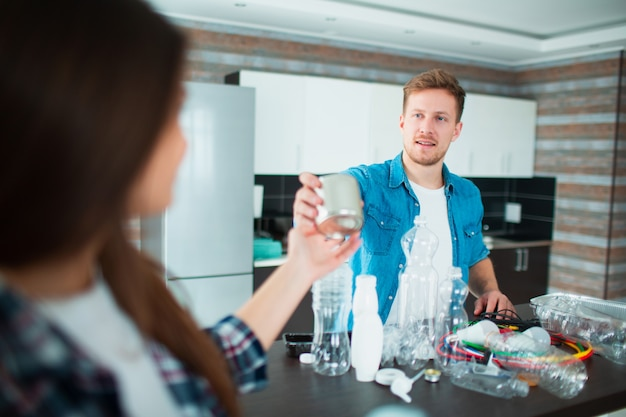 Молодая семья сортирует материалы на кухне для переработки. перерабатываемые материалы должны быть отделены. жена дает мужу старую консервную банку для продуктов. они сортируют весь мусор в доме