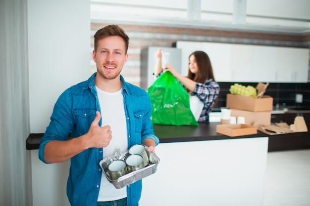 Молодая семья сортирует материалы на кухне для переработки. перерабатываемые материалы должны быть отделены. молодой человек держа старые жестяные коробки в ее руках для еды. на заднем плане сортированный мусор.