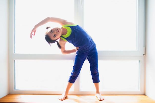 Маленькая девочка делает тренировки назад наклона стоя дома. милый парень тренируется на деревянном подоконнике в помещении. маленькая темноволосая модель в спортивной одежде делает упражнения возле окна в своей комнате