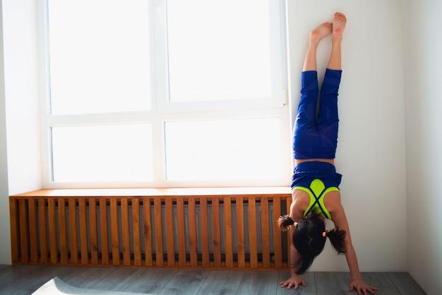 Маленькая девочка тренировки на дому. стойка для рук отжимания. милый парень стоит на руках у деревянного подоконника в помещении. маленькая темноволосая модель в спортивной одежде делает упражнения возле окна в своей комнате
