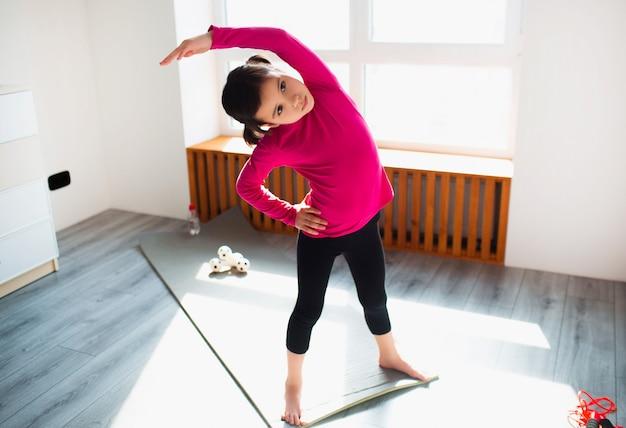 Маленькая девочка делает тренировки назад наклона стоя дома. милый парень тренируется на коврике в помещении. маленькая темноволосая модель в спортивной одежде делает упражнения возле окна в своей комнате.