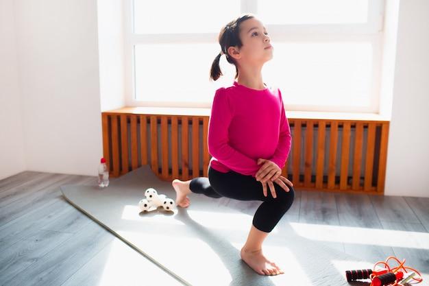 Маленькая девочка вперед выпад тренировки на дому. милый малыш тренируется на коврике в помещении. маленькая темноволосая модель в спортивной одежде делает упражнения возле окна в своей комнате