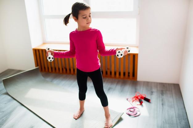 Маленькая девочка держит разминку гантелей спорт детей дома. милый малыш тренируется на коврике в помещении. маленькая темноволосая модель в спортивной одежде делает упражнения возле окна в своей комнате