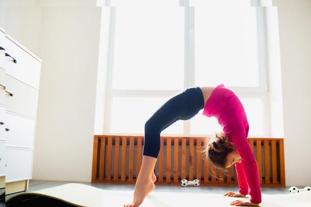 Разминка маленькой девочки дома в представлении моста. милый малыш тренируется на коврике в помещении. маленькая темноволосая модель в спортивной одежде делает упражнения возле окна в своей комнате