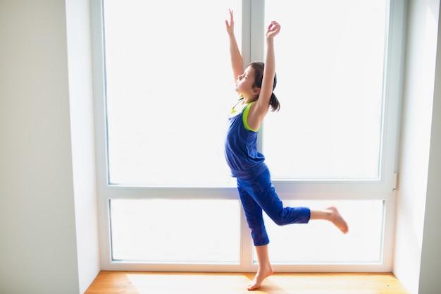 Маленькая девочка, достигнув тренировки дома. милый парень тренируется на деревянном подоконнике в помещении. маленькая темноволосая модель в спортивной одежде делает упражнения возле окна в своей комнате.