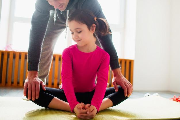 Маленькая девочка делает тренировки упражнения на растяжку дома. милый парень и папа тренируются на коврике в помещении. маленькая темноволосая модель в спортивной одежде делает упражнения возле окна в своей комнате