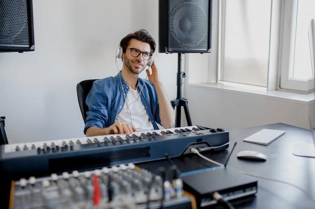 男が自宅のプロジェクトで電子サウンドトラックを制作