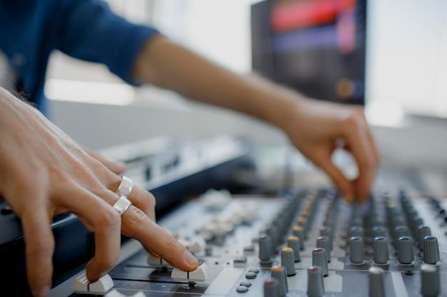 レコーディングスタジオのミキシングパネルで働くサウンドエンジニア