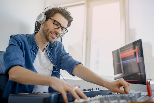 男はレコーディングスタジオでサウンドミキサーに取り組んでいます